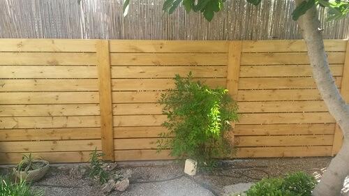 צביעת גדרות עץ בבית פרטי